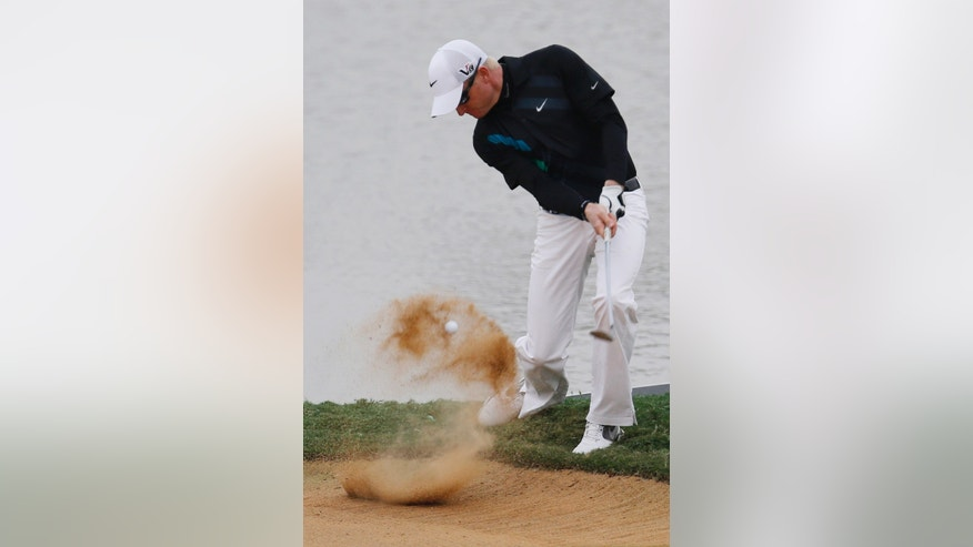 Simon Dyson of England hits out of a bunker on the 18th green during the second round of the BMW Masters golf tournament at the Lake Malaren Golf Club in Shanghai, China, Friday, Oct. 25, 2013. (AP Photo/Eugene Hoshiko)