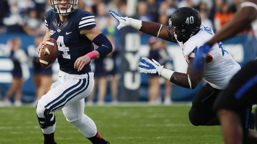 BYU's Taysom Hill (4) flees Boise State's Armand Nance (40) during an NCAA college football game, Friday, Oct. 25, 2013 at LaVell Edwards Stadium in Provo, Utah. (AP Photo/The Daily Herald, Mark Johnston)