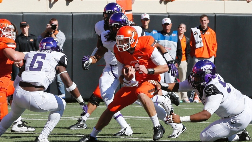 Oklahoma State quarterback J.W. Walsh, center, is stopped short of a touchdown by TCU defenders Elisha Olabode (6) and Davion Pierson (57) in the second quarter of an NCAA college football game in Stillwater, Okla., Saturday, Oct. 19, 2013. Oklahoma State won 24-10.(AP Photo/Sue Ogrocki)