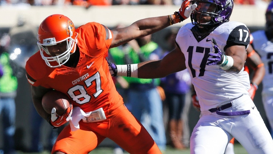 Oklahoma State wide receiver Tracy Moore (87) fends off TCU defender Sam Carter (17) in the second quarter of an NCAA college football game in Stillwater, Okla., Saturday, Oct. 19, 2013. Oklahoma State won 24-10. (AP Photo/Sue Ogrocki)