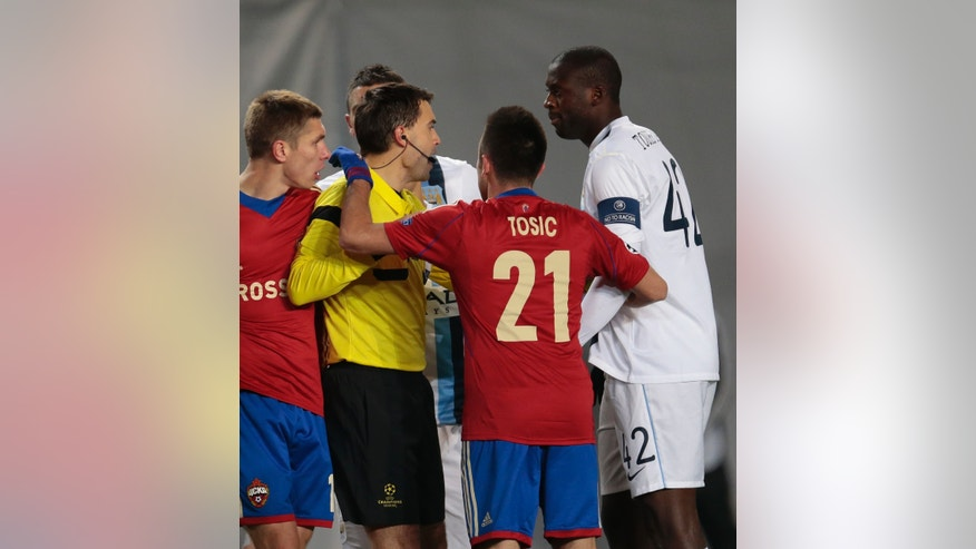 In this Wednesday, Oct. 23, 2103 photo, Manchester City's Yaya Toure, right, speaks to the referee Ovidiu Hategan, left, during the Champions League group D soccer match between CSKA Moscow and Manchester City, at Arena Khimki stadium outside Moscow, Russia, on Wednesday, Oct. 23, 2013. Manchester City midfielder Yaya Toure called on UEFA to take action against CSKA Moscow after he was subjected to racist chanting during his team's 2-1 win in the Champions League. The Ivory Coast player said he had told match referee Ovidiu Hategan about the chants during the game in the Russian capital. (AP Photo/Ivan Sekretarev)