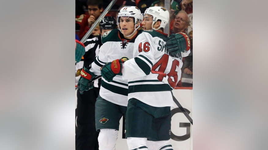 Minnesota Wild's Zach Parise (11), left, celebrates with Jared Spurgeon (46) after scoring a goal during the first period of an NHL hockey game against the Chicago Blackhawks in Chicago, Saturday, Oct. 26, 2013. (AP Photo/Nam Y. Huh)