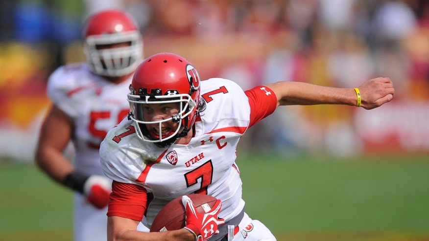 Utah quarterback Travis Wilson keeps the ball and rushes for a short-yardage first down during the first half of an NCAA college football game against Southern California, Saturday, Oct. 26, 2013, in Los Angeles. (AP Photo/Gus Ruelas)