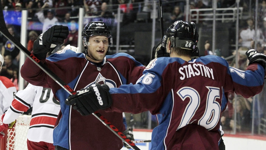 Colorado Avalanche defenseman Erik Johnson (6) celebrates scoring with Colorado Avalanche center Paul Stastny (26) against the Carolina Hurricanes  in the first period of an NHL hockey game in Denver on Friday, Oct. 25, 2013.(AP Photo/Joe Mahoney)