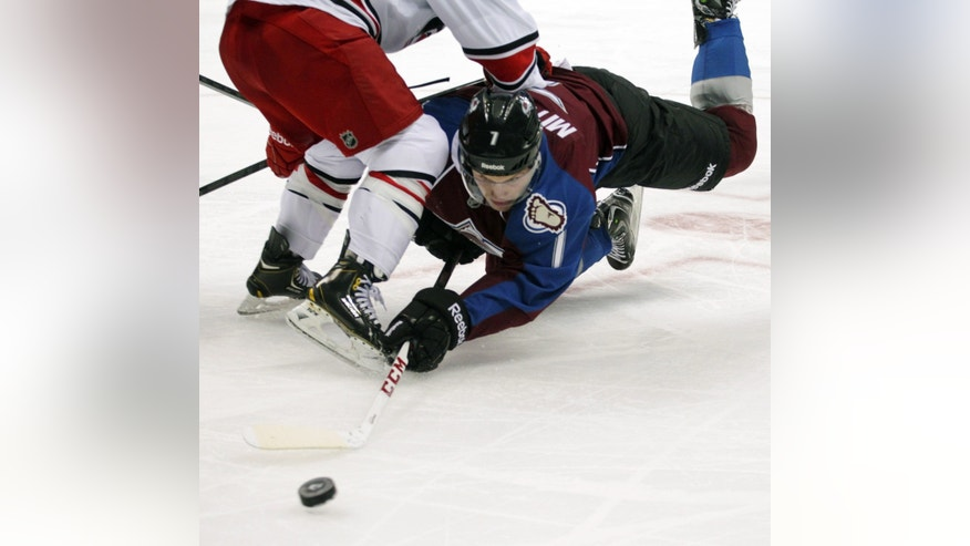 Colorado Avalanche center John Mitchell (7) dives for the puck against Carolina Hurricanes center Nathan Gerbe (14) in the second period of an NHL hockey game in Denver on Friday, Oct. 25, 2013.(AP Photo/Joe Mahoney)