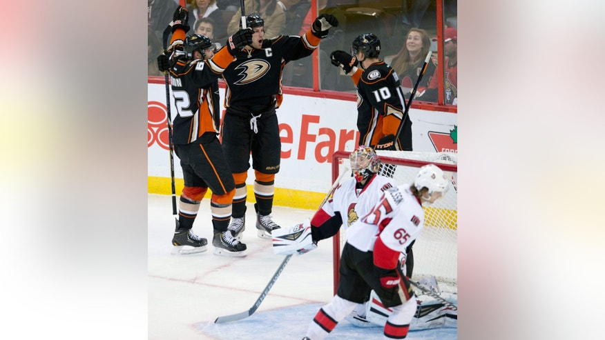 Ottawa Senators Erik Karlsson skates past goalie Craig Anderson as Anaheim Ducks center Ryan Getzlaf, center, celebrates his first period goal with teammates Patrick Maroon, left, and Corey Perry (10) during the first period of an NHL hockey game, Friday Oct. 25, 2013 in Ottawa, Ontario.  (AP Photo/The Canadian Press, Adrian Wyld)