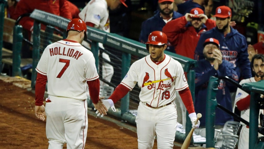 St. Louis Cardinals' Matt Holliday (7) is congratulated by Jon Jay after scoring during the first inning of Game 3 of baseball's World Series against the Boston Red Sox Saturday, Oct. 26, 2013, in St. Louis. (AP Photo/Charlie Neibergall)