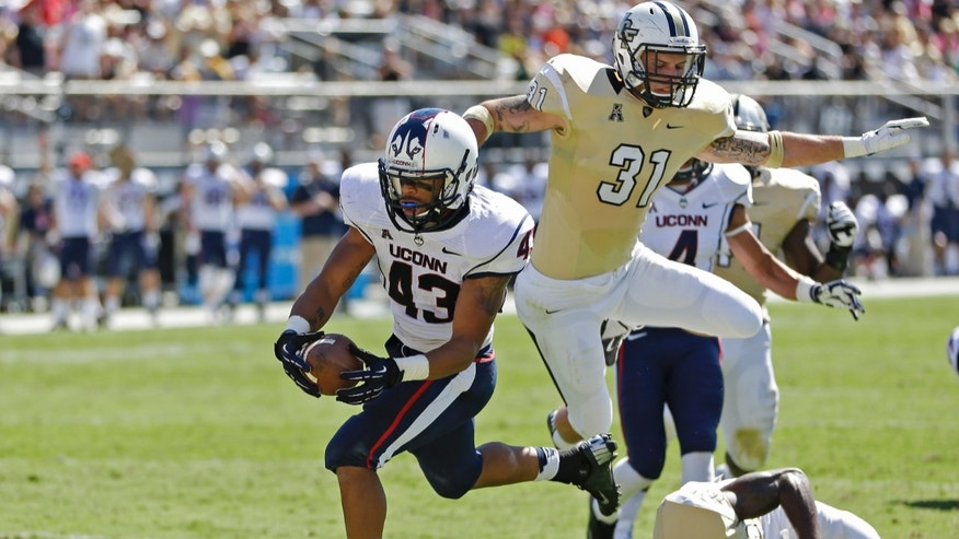 Connecticut running back Lyle McCombs (43) runs past Central Florida defensive backs Sean Maag (31) and Brandon Alexander (37) for a 9-yard touchdown during the first half of an NCAA college football game in Orlando, Fla., Saturday, Oct. 26, 2013.(AP Photo/John Raoux)