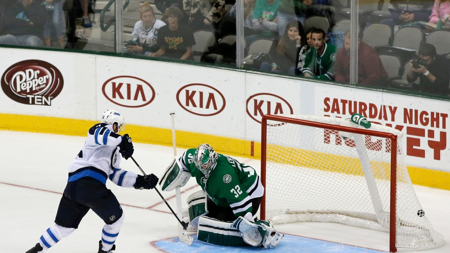 Winnipeg Jets left wing Andrew Ladd (16) scores a shootout goal against Dallas Stars goalie Kari Lehtonen (32), of Finland, in overtime of an NHL hockey game, Saturday, Oct. 26, 2013, in Dallas. The goal helped the Jets to the 2-1 win over the Stars. (AP Photo/Tony Gutierrez)