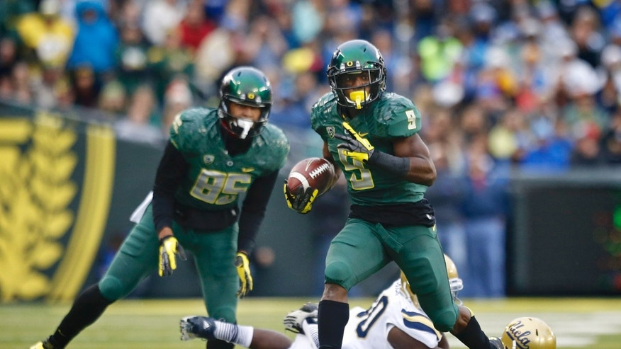 Oregon running back Byron Marshall (9) evades tackle and runs for a touchdown against UCLA in the second quarter of an NCAA college football game, Saturday, Oct. 26, 2013, in Eugene, Ore. (AP Photo/The Oregonian, Thomas Boyd)