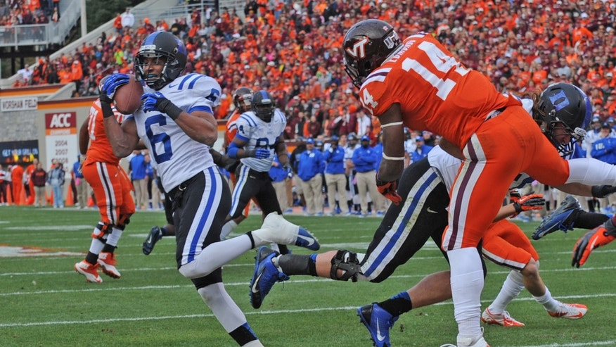 Duke defender Ross Cockrell (6) intercepts the ball in the end zone against Virginia Tech's Trey Edmonds (14) during the first half of an NCAA college football game in Blacksburg, Va., Saturday Oct. 26, 2013. (AP Photo/Don Petersen)