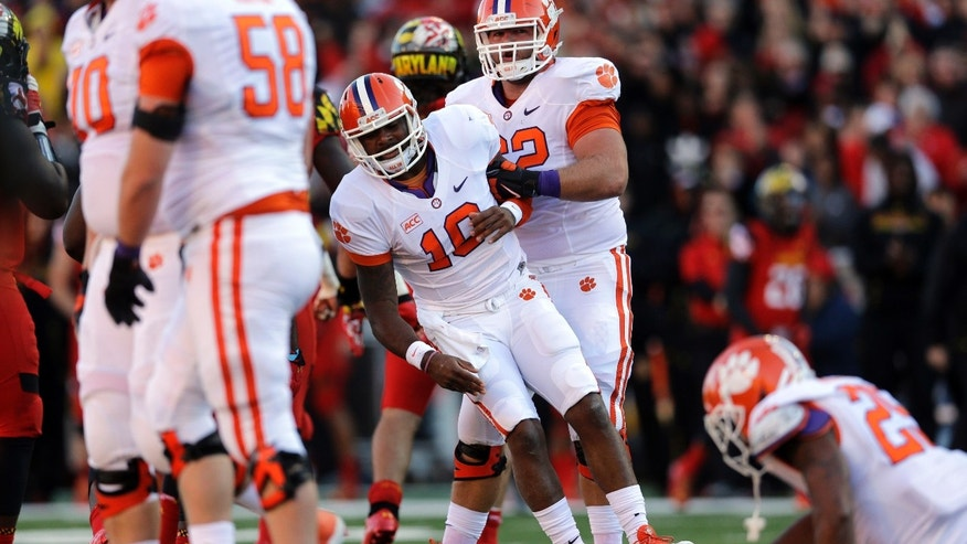 Clemson quarterback Tajh Boyd, center, is picked up by teammate Tyler Shatley after being sacked on a third down attempt in the first half of an NCAA college football game against Maryland in College Park, Md., Saturday, Oct. 26, 2013. (AP Photo/Patrick Semansky)