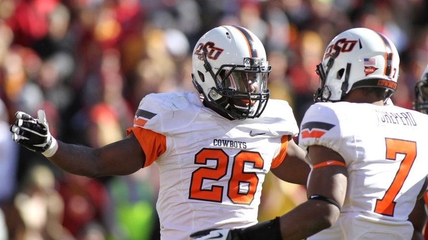Oklahoma State running back Desmond Roland celebrates with wide receiver Brandon Sheperd after one a touchdown run in the first half of an NCAA college football game against Iowa State in Ames, Iowa Saturday, Oct. 26, 2013. Roland rushed for 219 yards and four touchdowns in their 58-27 victory. (AP Photo by Justin Hayworth)
