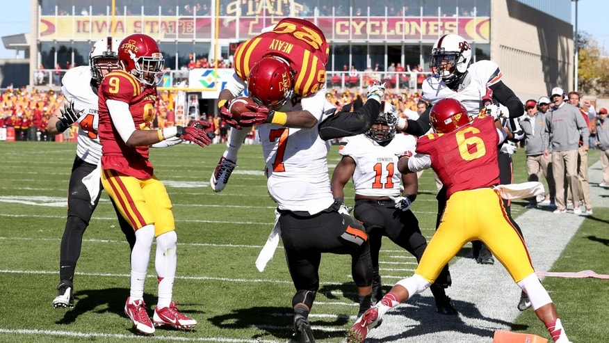 Iowa State running back DeVondrick Nealy (20) jumps over the top of Oklahoma State safety Shamiel Gary (7) to score a touchdown during the first half of an NCAA college football game in Ames, Iowa Saturday, Oct. 26, 2013.(AP Photo by Justin Hayworth)