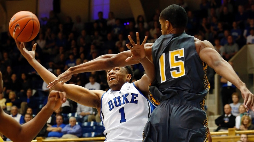 Duke's Jabari Parker (1) drives the basket as Bowie State's Brian Freeman (15) defends during the first half of an exhibition NCAA college basketball game in Durham, N.C., Saturday, Oct. 26, 2013. (AP Photo/Karl B. DeBlaker)