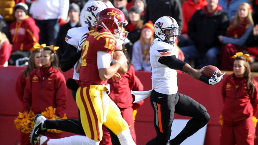 Oklahoma State cornerback Justin Gilbert (4) makes his way into the end zone for a touchdown after picking off a pass from Iowa State quarterback Sam B. Richardson (12) during the first half of an NCAA college football game in Ames, Iowa Saturday, Oct. 26, 2013.(AP Photo by Justin Hayworth)