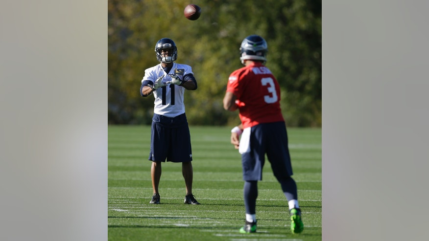 Seattle Seahawks wide receiver Percy Harvin (11) catches a pass from quarterback Russell Wilson (3) as they take part in NFL football practice, Tuesday, Oct. 22, 2013, in Renton, Wash. It was Harvin's first full team practice since he injured his hip during the off-season. (AP Photo/Ted S. Warren)