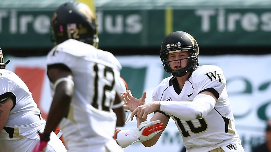 Wake Forest quarterback Tanner Price (10) passes to Tyree Harris (12) during the first half of an NCAA college football game against Miami in Miami Gardens, Fla., Saturday, Oct. 26, 2013. (AP Photo/J Pat Carter)