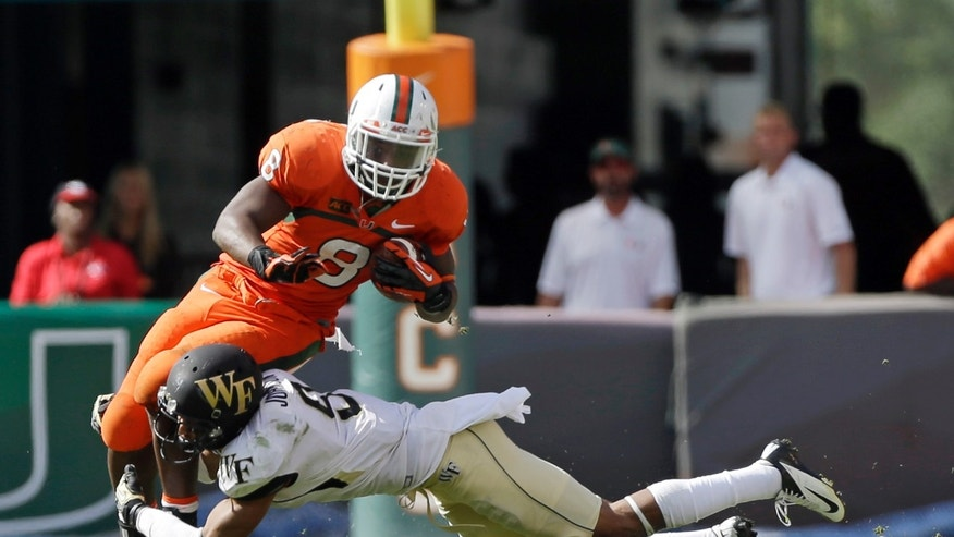 Miami's Duke Johnson (8) is tackled by Wake Forest's Kevin Johnson (9) in the second half of an NCAA college football game, Saturday, Oct. 26, 2013, in Miami Gardens, Fla. Miami won 24-21. (AP Photo/Alan Diaz)