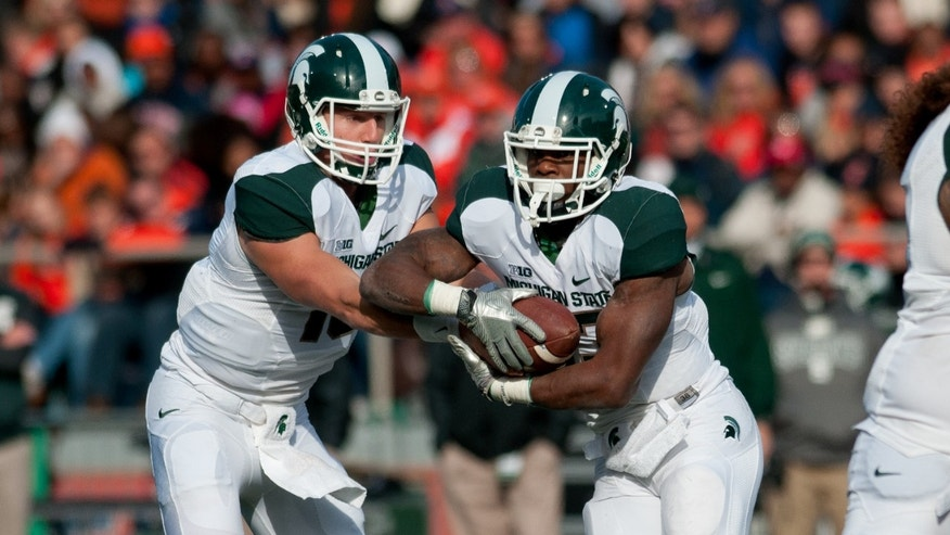 Michigan State quarterback Connor Cook (18) hands the ball off to running back Jeremy Langford (33) against Illinois during the first quarter of an NCAA college football game, Saturday, Oct. 26, 2013 at Memorial Stadium in Champaign, Ill. (AP Photo/Bradley Leeb)