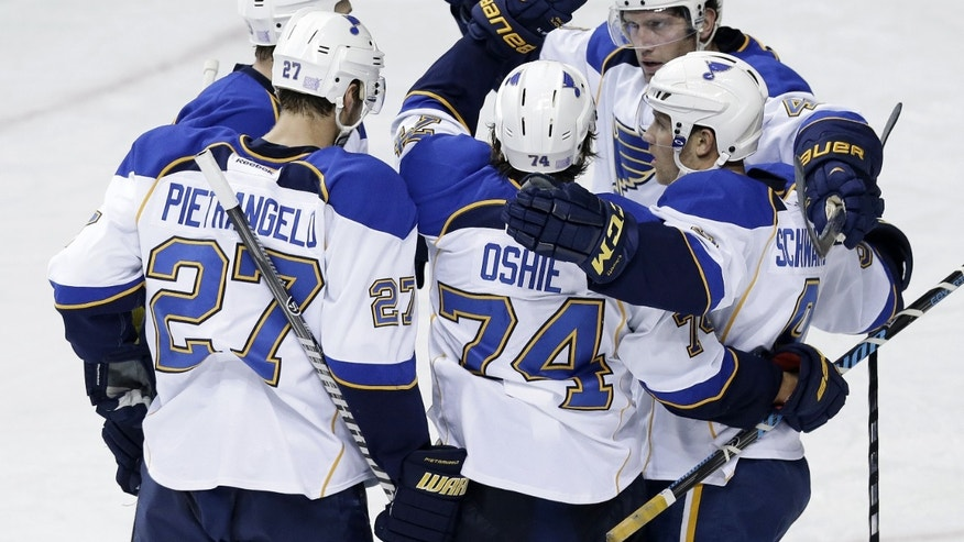 St. Louis Blues center T.J. Oshie (74) celebrates with Alex Pietrangelo (27), David Backes (42) and Jaden Schwartz (9) after scoring against the Nashville Predators in the second period of an NHL hockey game on Saturday, Oct. 26, 2013, in Nashville, Tenn. (AP Photo/Mark Humphrey)