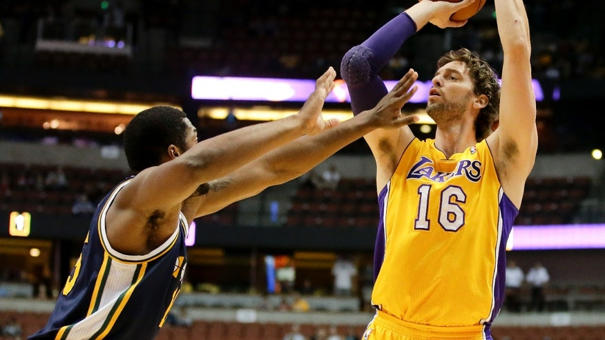Los Angeles Lakers forward Pau Gasol, right, shoots over Utah Jazz forward Derrick Favors during the first half of a preseason NBA basketball game in Anaheim, Calif., Friday, Oct. 25, 2013. (AP Photo/Chris Carlson)