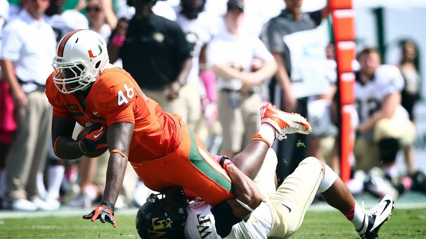Wake Forest's Ryan Janvion (22) tackles Miami's Clive Walford (46) during the first half of an NCAA college football game in Miami Gardens, Fla., Saturday, Oct. 26, 2013. (AP Photo/J Pat Carter)