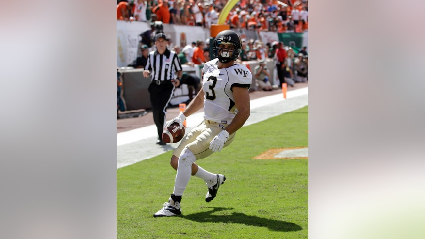 Wake Forest's Michael Campanaro (3) scores a touchdown against Miami in the first half of an NCAA college football game, Saturday, Oct. 26, 2013, in Miami Gardens, Fla. (AP Photo/Alan Diaz)