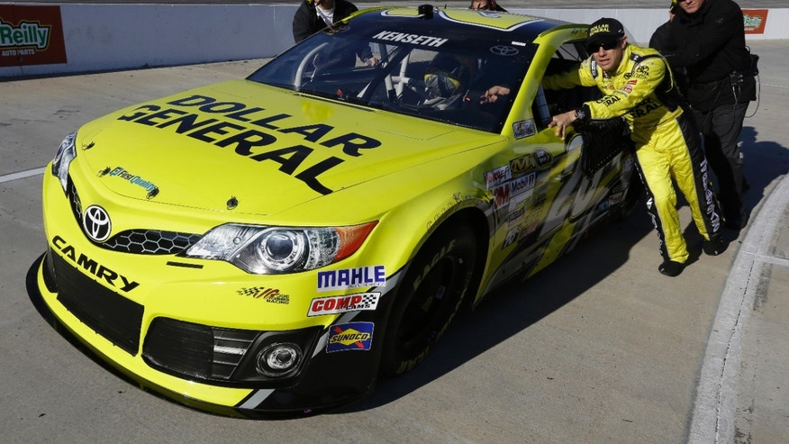 Matt Kenseth helps push his car on pit row during qualifying for Sunday's NASCAR Sprint Cup series auto race at Martinsville Speedway in Martinsville, Va., Friday, Oct. 25, 2013. (AP Photo/Steve Helber)