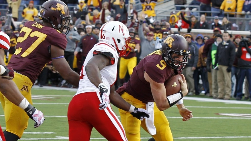 Minnesota quarterback Philip Nelson (9) carries the ball into the end zone for a touchdown during the fourth quarter of an NCAA college football game against Nebraska in Minneapolis Saturday, Oct. 26, 2013. Minnesota beat Nebraska 34-23. (AP Photo/Ann Heisenfelt)