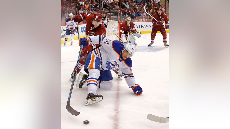 Edmonton Oilers' Nail Yakupov (64), of Russia, battles Phoenix Coyotes' Antoine Vermette for the puck during the first period of an NHL hockey game Saturday, Oct. 26, 2013, in Glendale, Ariz. (AP Photo/Matt York)