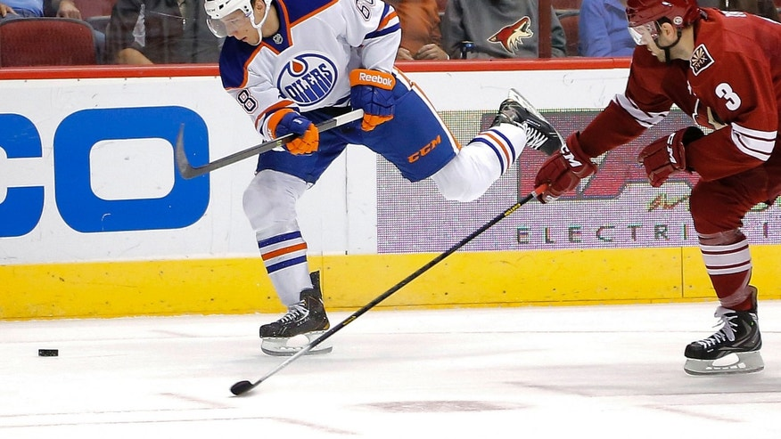 Edmonton Oilers' Tyler Pitlik, left, scores on a shot as Phoenix Coyotes' Keith Yandle defends during the first period of an NHL hockey game, Saturday, Oct. 26, 2013, in Glendale, Ariz. (AP Photo/Matt York)