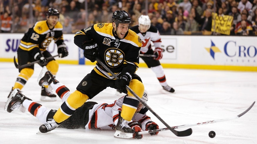 Boston Bruins' Gregory Campbell cuts pas sprawling New Jersey Devils defenseman Eric Gelinas during the second period of an NHL hockey game in Boston, Saturday, Oct. 26, 2013. (AP Photo/Winslow Townson)