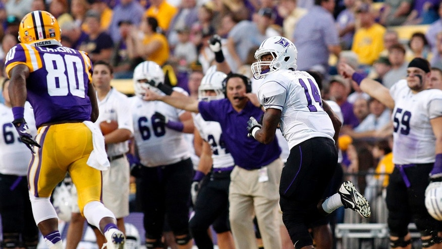Furman cornerback Reggie Thomas (14) returns an interception for a 74- yard tuchdown during the first quarter of the NCAA college football game against LSU in Baton Rouge, La., Saturday, Oct, 26, 2013. (AP Photo/Jonathan Bachman)