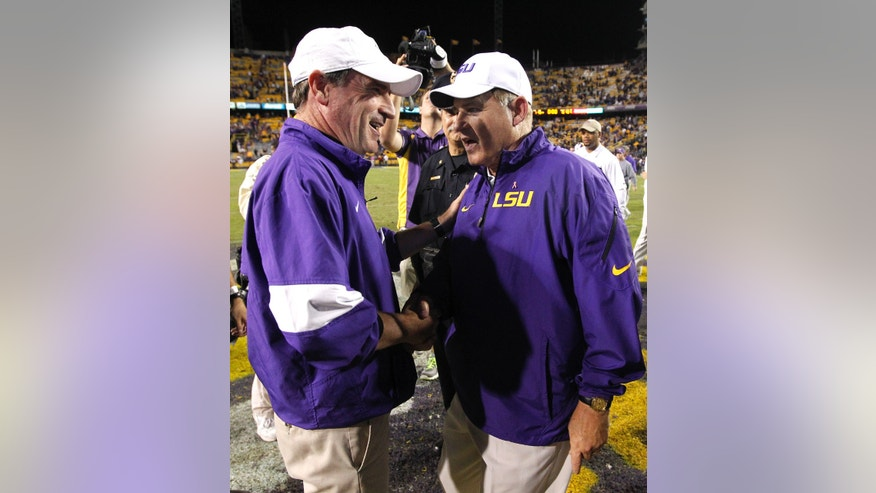 LSU head coach Les Miles greets Furman head coach Bruce Fowler after the NCAA college football game in Baton Rouge, La., Saturday, Oct, 26, 2013. LSU won 48-16. (AP Photo/Jonathan Bachman)