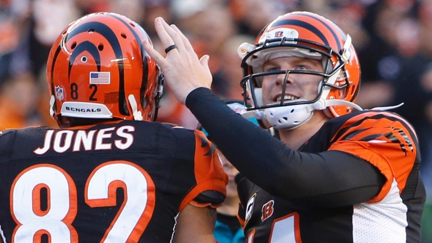 Cincinnati Bengals quarterback Andy Dalton (14) congratulates wide receiver Marvin Jones (82) after they combined on their third touchdown pass of the game in the first half of an NFL football game against the New York Jets, Sunday, Oct. 27, 2013, in Cincinnati. (AP Photo/David Kohl)
