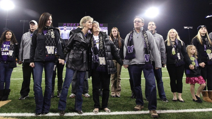 Carol James, center right, wife of former head football coach Don James,  is embraced by their daughter Jill Woodruff as other daughter Jeni Simmons and son Jeff James stand with them and other family members Saturday, Oct. 26, 2013, before an NCAA college football game against California in Seattle. James died Sunday, Oct. 20. (AP Photo/Elaine Thompson)