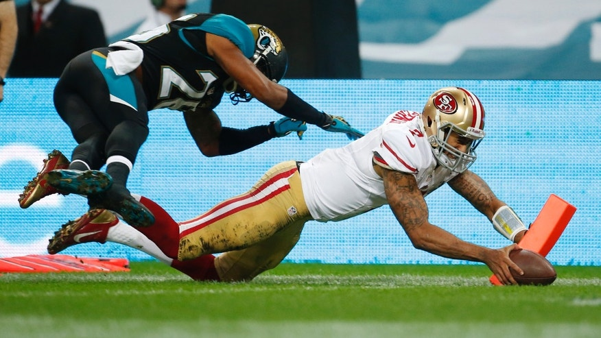 San Francisco 49ers quarterback Colin Kaepernick (7) scores a 12-yard touchdown while being pursued by Jacksonville Jaguars free safety Josh Evans (26) during the NFL football game at Wembley Stadium, London, Sunday, Oct. 27, 2013.  (AP Photo/Matt Dunham)