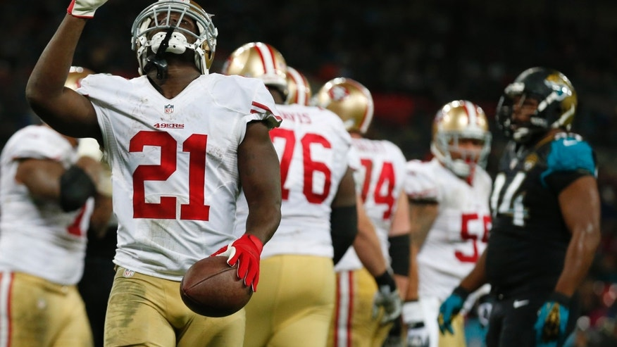 San Francisco 49ers running back Frank Gore (21) points upwards after a two-yard touchdown run during the second half of an NFL football game against the Jacksonville Jaguars at Wembley Stadium, London, Sunday, Oct. 27, 2013.  (AP Photo/Matt Dunham)