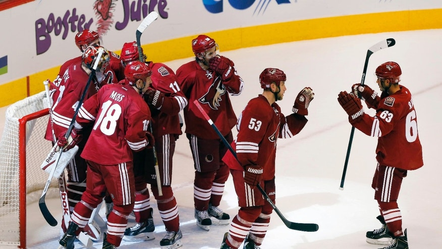 Phoenix Coyotes' Mike Ribeiro (63), Derek Morris (53), Antoine Vermete, third from right, Martin Hanzal (11), David Moss (18) goalie Mike Smith, and Oliver Ekman-Larsson celebrate their win over the Edmonton Oilers after an NHL hockey game Saturday, Oct. 26, 2013, in Glendale, Ariz. The Coyotes won 5-4. (AP Photo/Matt York)