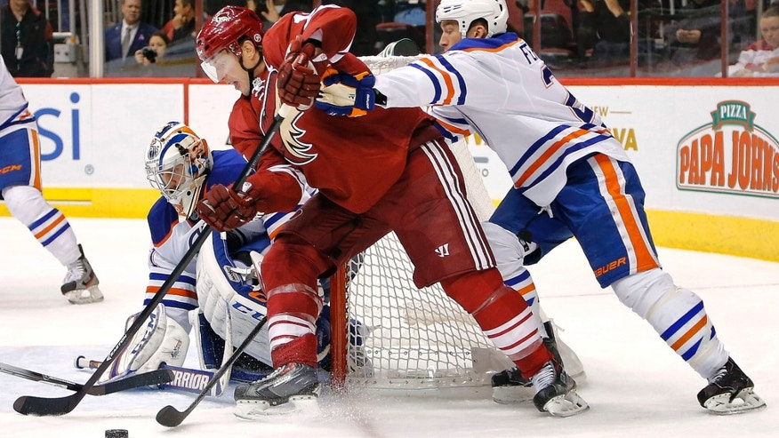 Phoenix Coyotes' Shane Doan, center, battles Edmonton Oilers' Andrew Ference, right, as Oilers' goalie Jason LaBarbera defends during the second period of an NHL hockey game Saturday, Oct. 26, 2013, in Glendale, Ariz. (AP Photo/Matt York)