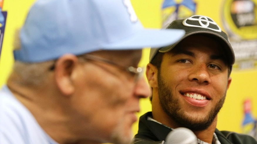 Darrell Wallace Jr., right, winner of Saturday's NASCAR Camping World Truck race, smiles as he listens to Wendell Scott Jr., left, during a news conference at Martinsville Speedway in Martinsville, Va., Sunday, Oct. 27, 2013. (AP Photo/Steve Helber)