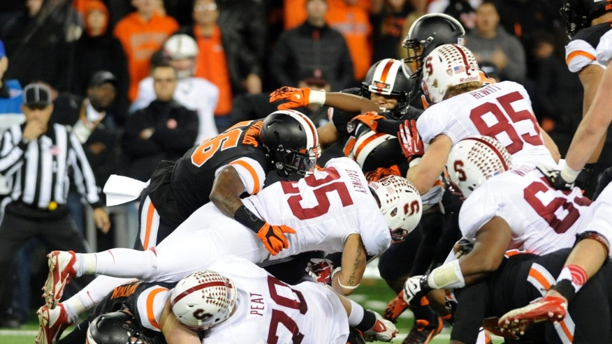 Stanford's Tyler Gaffney (25) works against Oregon State defenders during the first half of an NCAA college football game in Corvallis, Ore., Saturday Oct. 26, 2013. (AP Photo/Greg Wahl-Stephens)
