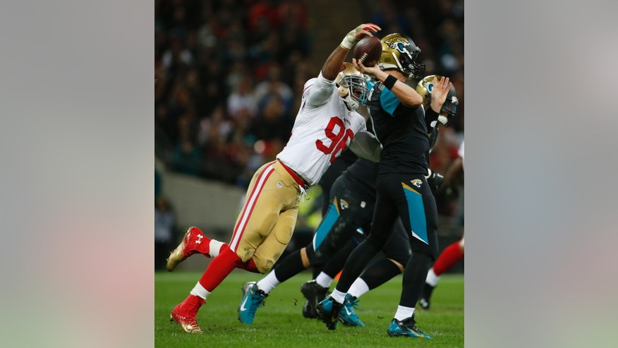 San Francisco 49ers linebacker Corey Lemonier (96) tries to knock the ball out of Jacksonville Jaguars quarterback Chad Henne's hand during the first half of an NFL football game at Wembley Stadium, London, Sunday, Oct. 27, 2013.  (AP Photo/Matt Dunham)