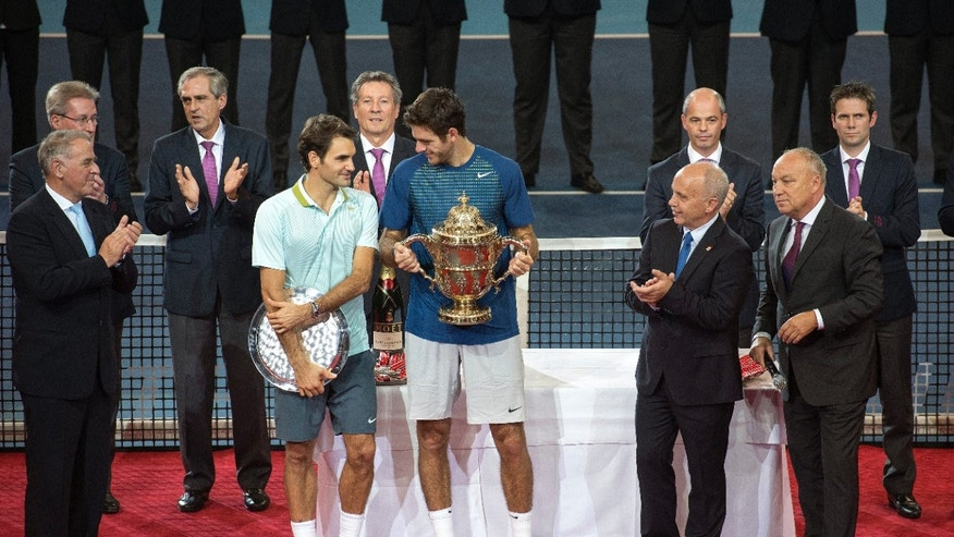 Switzerland's Roger Federer, center left, and winner  Argentina's Juan Martin Del Potro,  center right, attend  the awarding ceremony of  the Swiss Indoors tennis tournament at the St. Jakobshalle in Basel, Switzerland, on Sunday, Oct. 27, 2013. (AP Photo/Keystone,Georgios Kefalas)