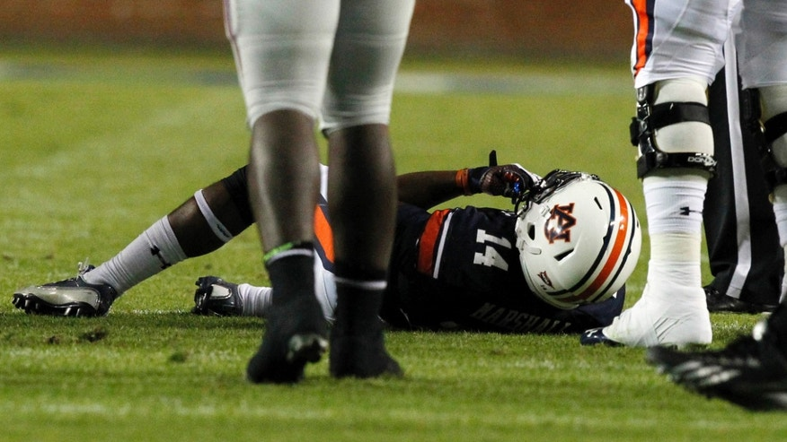 Auburn quarterback Nick Marshall (14) lies on the ground after sustaining an injury during the first half of an NCAA college football game against Florida Atlantic on Saturday, Oct. 26, 2013, in Auburn, Ala. (AP Photo/Butch Dill)