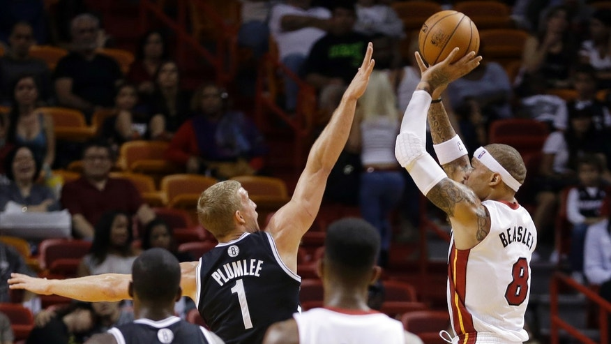 Miami Heat small forward Michael Beasley (8) prepares to take a shot as Brooklyn Nets power forward Mason Plumlee (1) defends in the fourth quarter of an NBA preseason basketball game, Friday, Oct. 25, 2013, in Miami. The Nets won 108-87. (AP Photo/Alan Diaz)