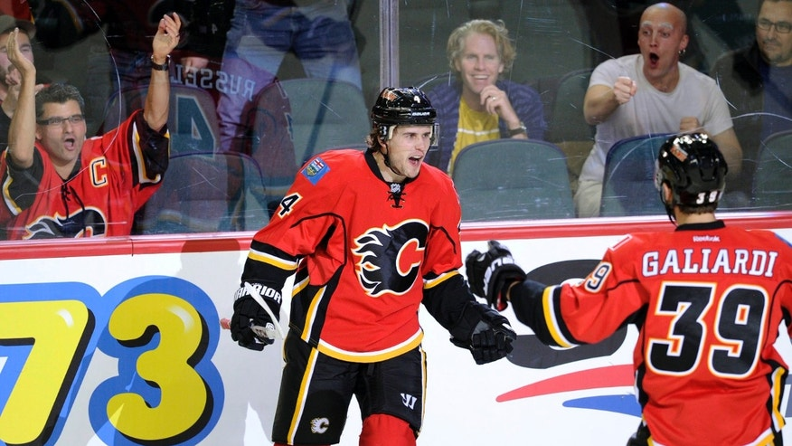 Calgary Flames' Kris Russell, left, celebrates his goal against the Washington Capitals with teammate TJ Galiardi during the first period of an NHL hockey game, in Calgary, Alberta, Saturday, Oct. 26, 2013. (AP Photo/The Canadian Press, Larry MacDougal)
