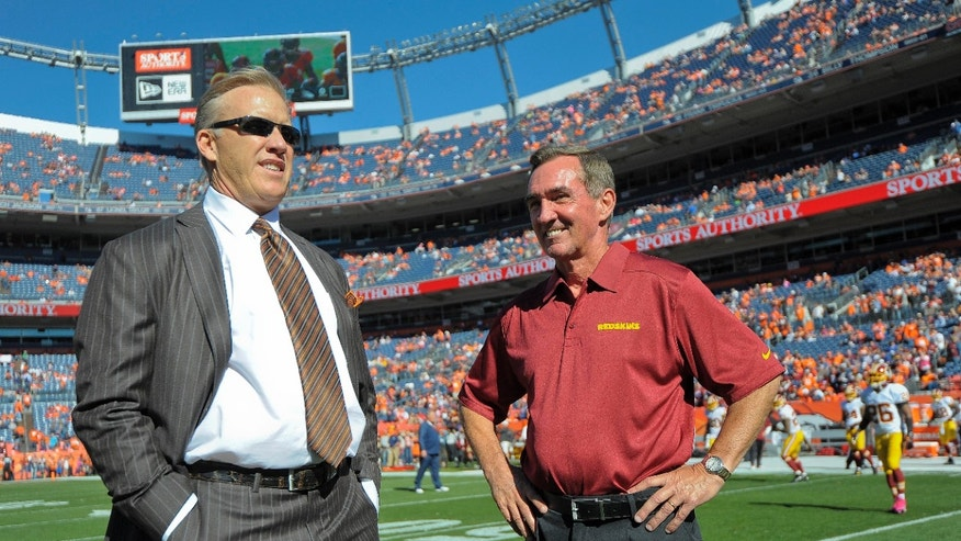 Denver Broncos executive vice president of football operations John Elway, left, talks with Washington Redskins coach Mike Shanahan before an NFL football game, Sunday, Oct. 27, 2013, in Denver. (AP Photo/Jack Dempsey)