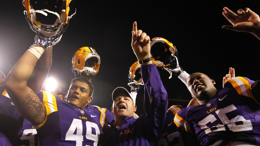 LSU head coach Les Miles, LSU fullback Melvin Jones (49), and LSU offensive tackle Jerald Hawkins (65) celebrate their victory over Furman after the NCAA college football game in Baton Rouge, La., Saturday, Oct, 26, 2013. LSU won 48-16. (AP Photo/Jonathan Bachman)
